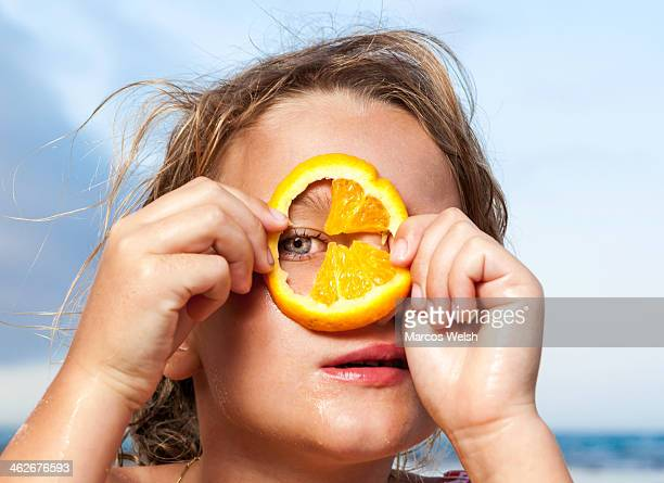 Young girl looking through slice of orange