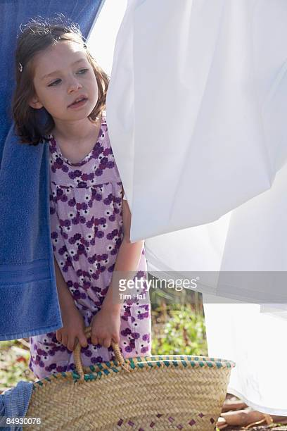 Young girl looking through washing
