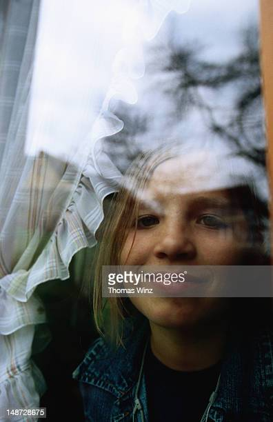 Young girl looking through window.