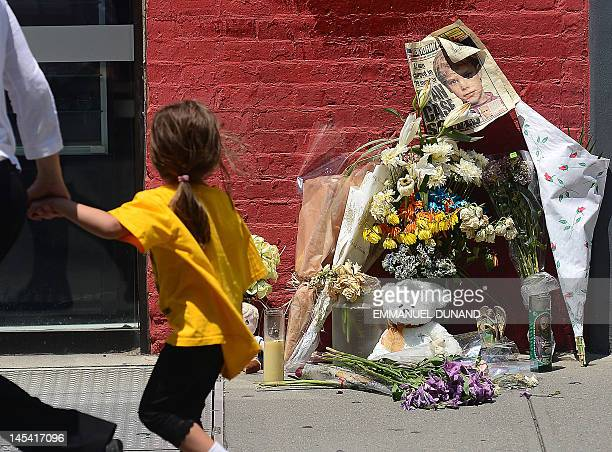 A young girl looks at a street shrine to sixyearold Etan Patz who disappeared 33 years ago set in front of the building where suspect Pedro Hernandez...