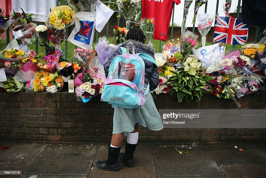 A young girl looks at floral tributes close to the scene where Drummer Lee Rigby of the 2nd Battalion the Royal Regiment of Fusiliers was killed, on May 24, 2013 in London, England. Drummer Lee Rigby of the 2nd Battalion the Royal Regiment of Fusiliers was murdered by suspected Islamists near London's Woolwich Army Barracks. The UK's security services are facing a Commons inquiry after confirmation that the two men arrested were known to MI5.