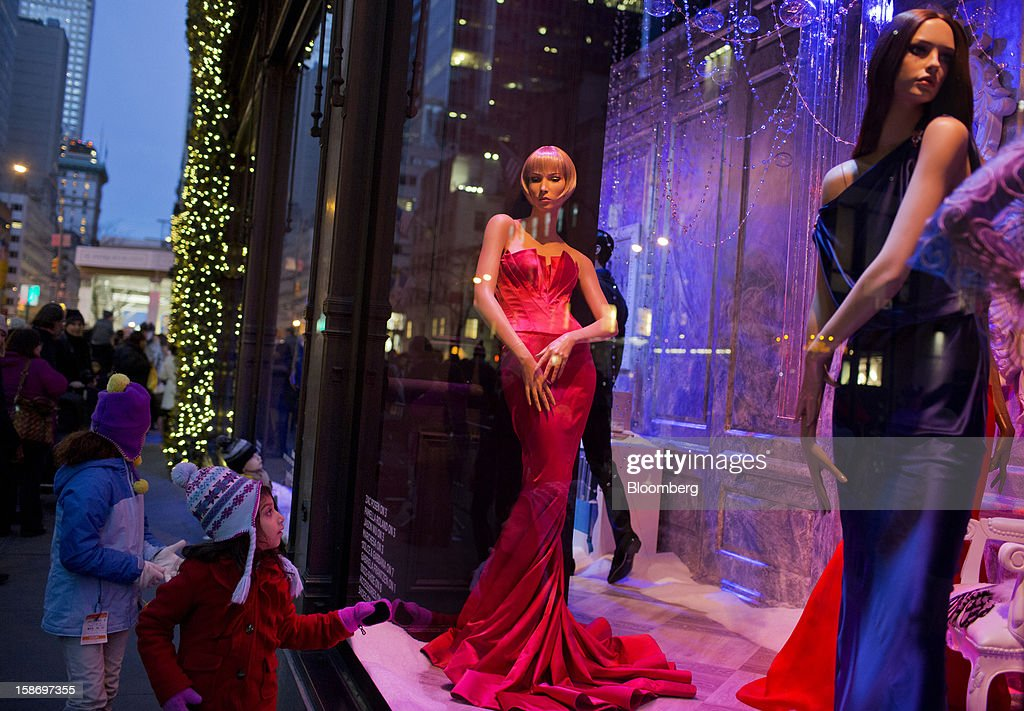 A young girl looks at mannequins in long gowns inside a Saks Fifth Avenue holiday window display in New York, U.S., on Sunday, Dec. 23, 2012. Holiday shoppers descended on U.S. stores this weekend in a last-minute dash to buy gifts amid concerns about the nation's economy and the impasse in Washington over taxes and spending. Photographer: Victor J. Blue/Bloomberg via Getty Images