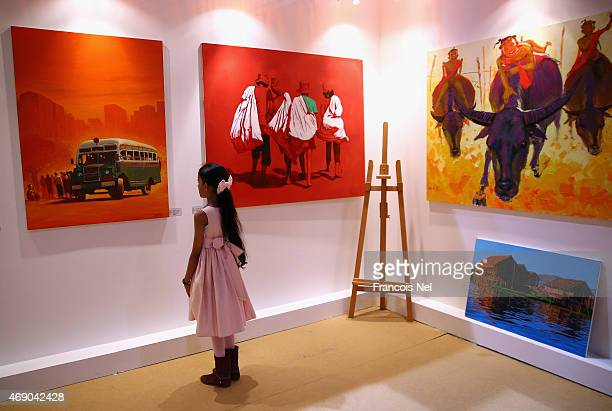 A young girl looks at the work of artist Sathar Al Karan during World Art Dubai 2015 at Dubai World Trade Centre on April 9 2015 in Dubai United Arab...