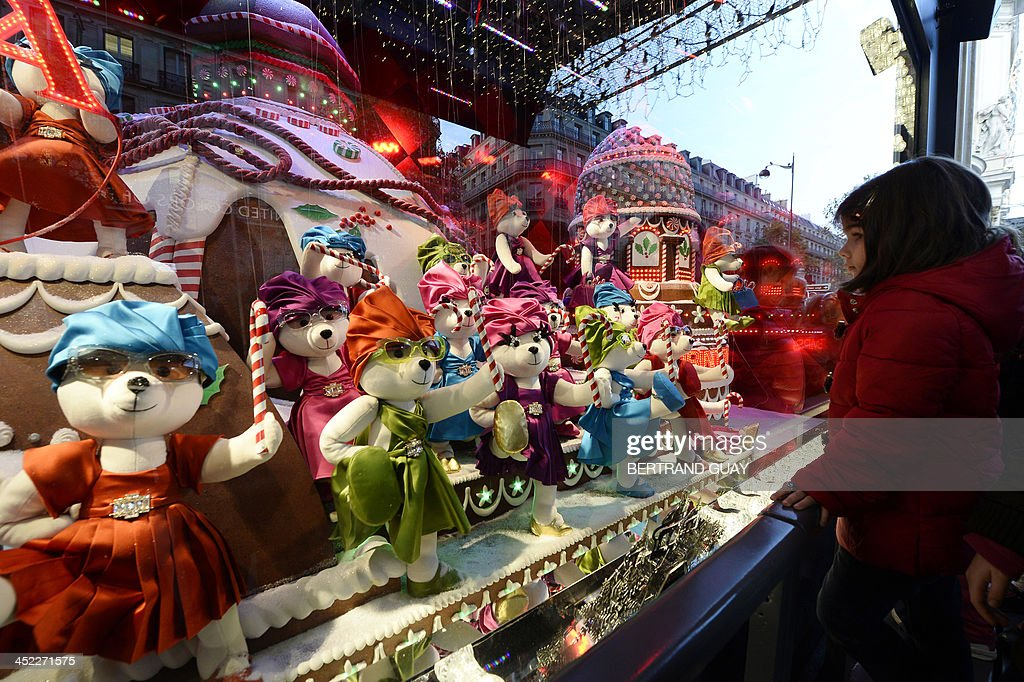 A young girl looks at toys exhibited in a Christmas window of Paris department store 'Printemps' on November 27, 2013.