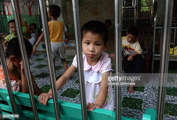 A young girl looks at visitors inside a staterun orphanage in Ba Vi district in the outskirts of Hanoi on September 16 2014US parents will be allowed...