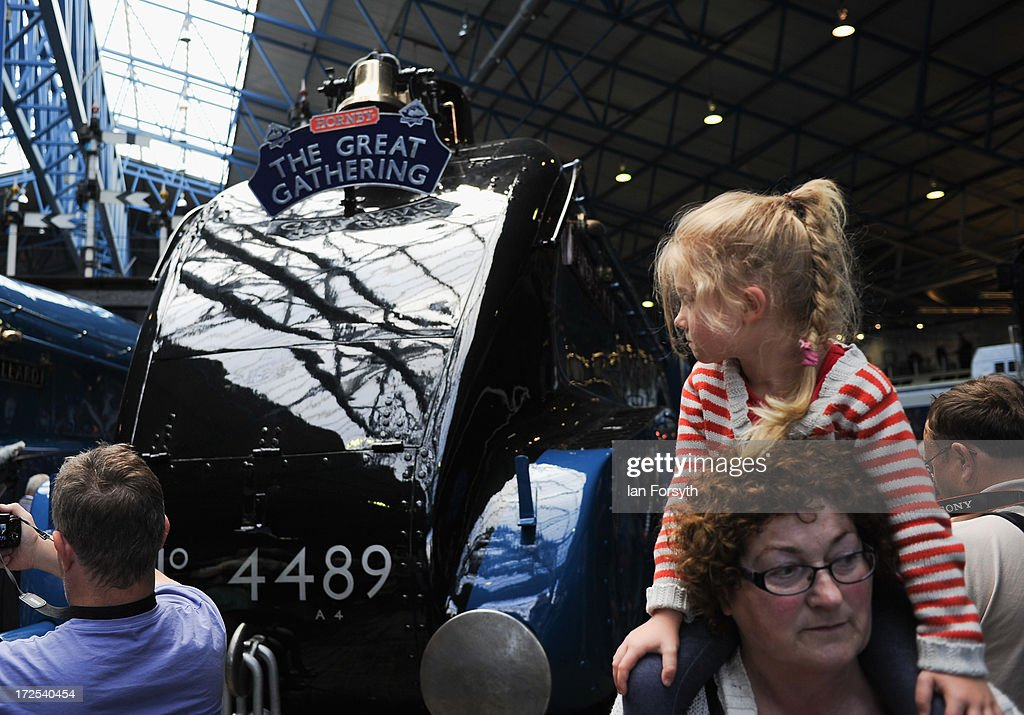A young girl looks back at the line up of steam locomotives at the National Railway Museum on July 3, 2013 in York, England. The National Railway Museum's 'Great Gathering' marks 75 years since the world's fastest steam locomotive, Mallard, is reunited with its five sister locomotives on the anniversary of its world record breaking run in 1938 where the Doncaster built steam legend raced into the record books at Stoke Bank near Grantham. The other locomotives were Sir Nigel Gresley, Dwight d Eisenhower, Union of South Africa, Bittern and the Dominion of Canada.