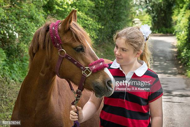 Young girl looks lovingly at her pony