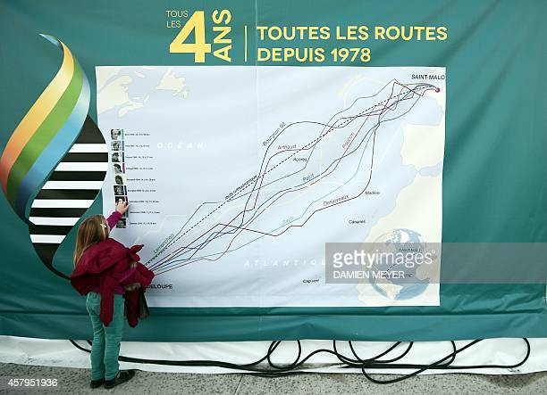 A young girl looks on giant map showing 'Route du Rhum' winners' routes October 27 2014 in Saint Malo western France before the 10th edition of the...