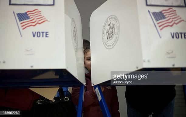 A young girl looks out from a privacy booth as her parents vote on November 6 2012 in the Staten Island borough of New York City As Staten Island...