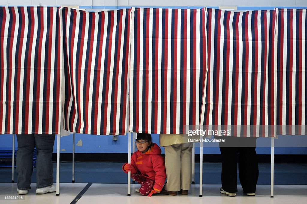 A young girl looks out from a voting booth as her mother casts her ballot at the Bishop Leo O'Neil Youth Center on November 6, 2012 in Manchester, New Hampshire. The swing state of New Hampshire is recognised to be a hotly contested battleground that offers 4 electoral votes, as recent polls predict that the race between U.S. President Barack Obama and Republican presidential candidate Mitt Romney remains tight.