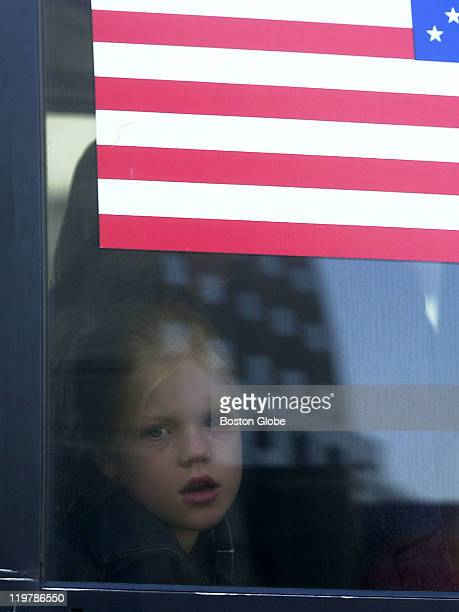 A young girl looks out through a window in a bus carrying the relatives of victims of Sept 11 as the image of a building is reflected on the window...