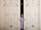 young girl looks through a big wooden slide door