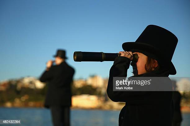 A young girl looks through a telescope a sshe joins black suited and top hat wearing teenagers from Newington College as they form the human...