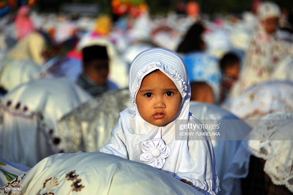 A young girl looks up as Indonesian Muslims take part in special morning prayers near the Bajrah Sandhi monument in Denpasar on Indonesia's island of Bali on August 8, 2013. Muslims around the world will celebrate Eid al-Fitr this week, marking the end of holiest month of Ramadan during which followers are required to abstain from food, drink and sex from dawn to dusk.