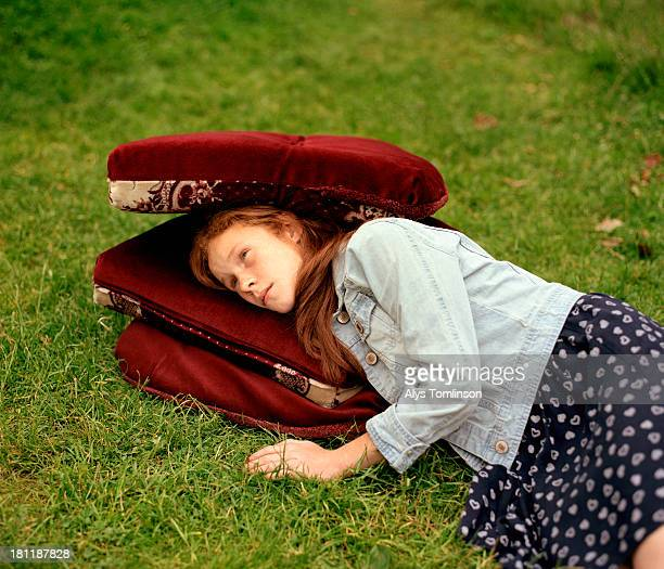 Young girl lying down on cushions outdoors
