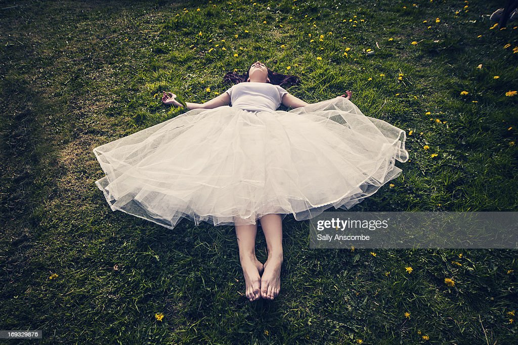 Young girl lying down on the grass
