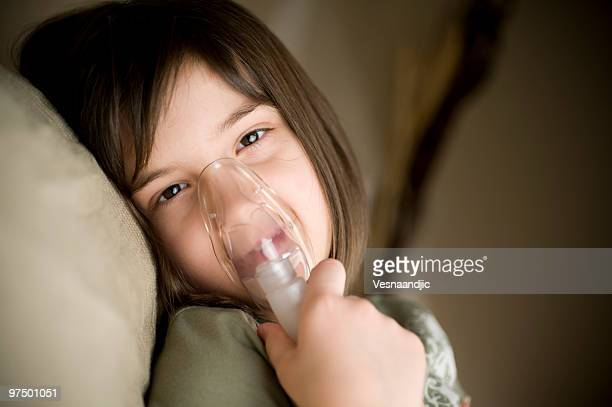 Young girl lying down using an inhaler device