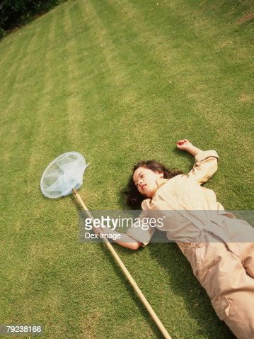 Young girl lying on grass holding a Butterfly net : Stock Photo