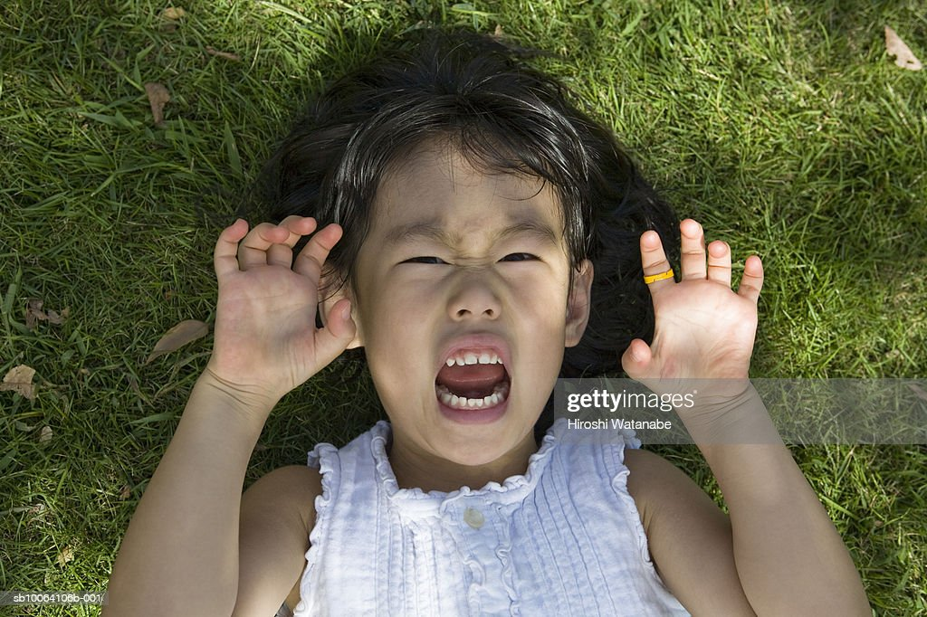 Young girl (4-5) lying on grass, making face, overhead view : Stock Photo