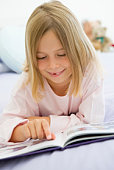 Young Girl Lying On Her Bed In Her Pajamas, Reading A Book