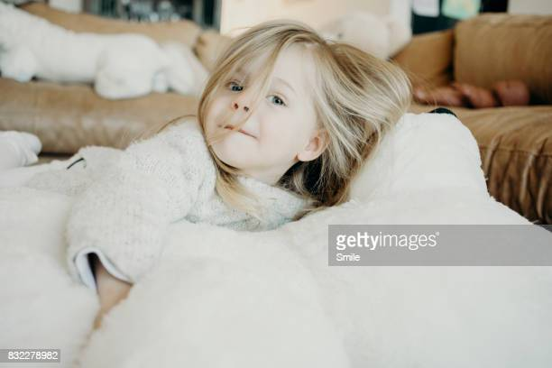 Young girl lying on large teddy bear looking at camera