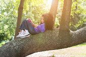 Young girl lying on tree branch reading book
