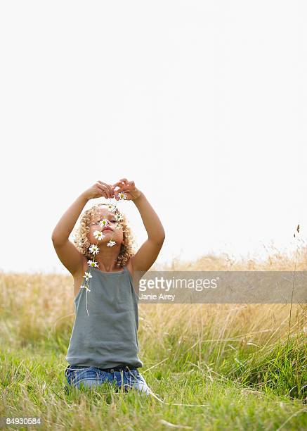 Young girl making a daisy chain in field