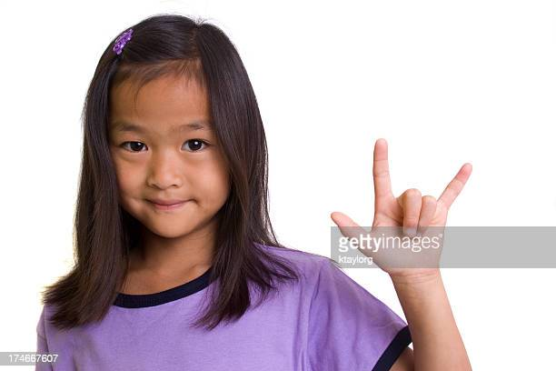 A young girl making an I love you hand sign
