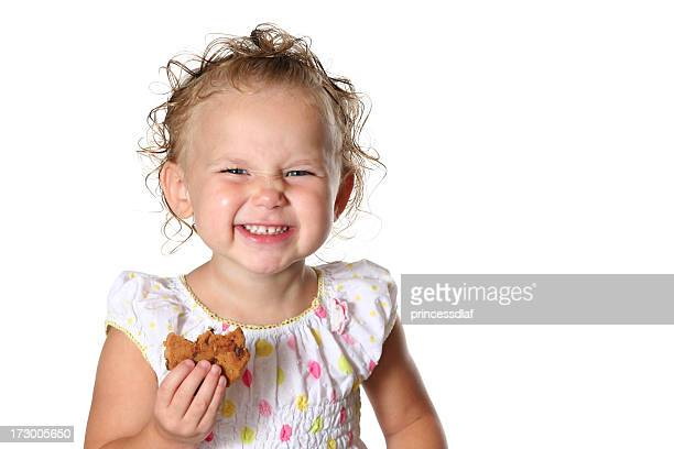 Young girl making faces holding a cookie