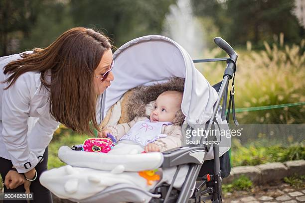 Young girl making faces to her baby in a stroller