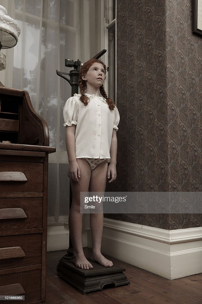 Young girl measuring her height : Stock Photo