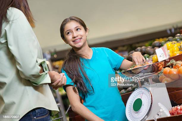 Young girl measuring tomatoes with mom at supermarket