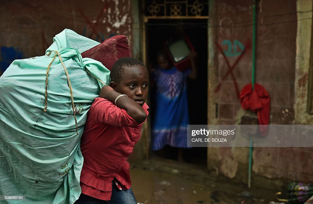 A young girl moves her belongings from a block of flats which is going to be demolished in the Huruma neighbourhood of Nairobi on May 6, 2016. Following a building collapse which claimed at least 40 lives with more 80 people still unaccounted for, after severe flooding, the government has ordered the demolition of similar unsafe buildings in the area. Located in the poor, tightly-packed Huruma neighbourhood, the building, which housed around 150 families crammed into single rooms, had been slated for demolition after being declared structurally unsound. But an evacuation order for the structure, which was built next to a river just two years ago, was ignored. / AFP / CARL