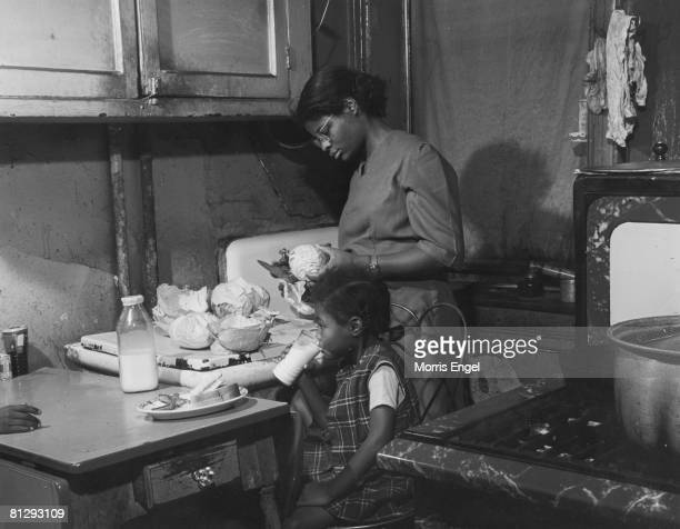 A young girl named 'Rebecca' sits at a kitchen table and drinks a glass of milk as her mother prepares food in their kitchen at home in Harlem New...