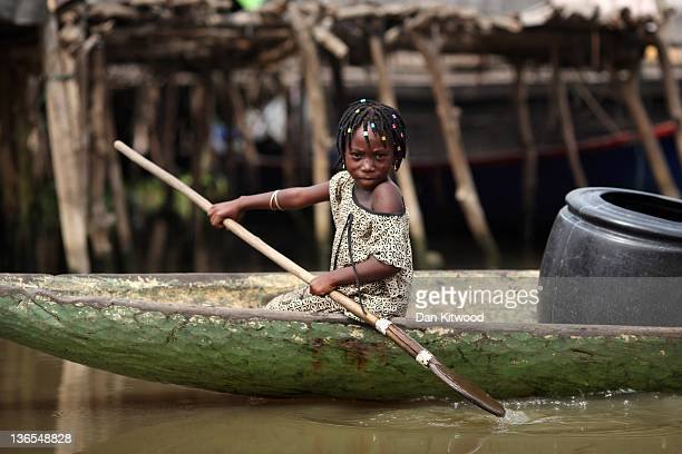 A young girl navigates their way through Ganvie in her boat on January 6 2012 in Cotonou Benin Often called the Venice of Africa Ganvie is a stilted...