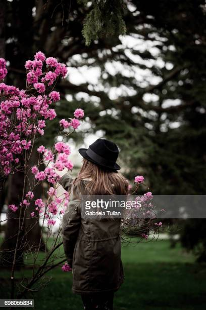 Young girl near the blooming tree in spring time