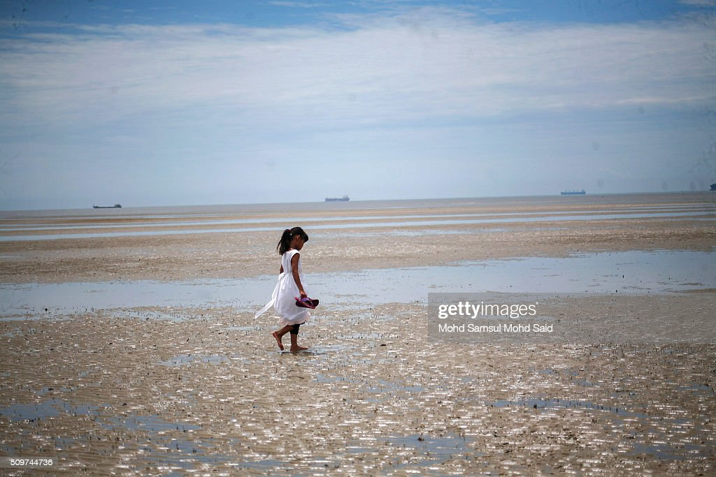 A young girl of the Mah Meri tribe walk towards the beach for their 'Puja Pantai', a thanksgiving ritual to appease the spirits of the seas at Straits of Malacca beach on February 12, 2016 in Pulau Carey, Malaysia. Every year, the indigenous people of Mah Meri village, located in Pulau Carey, about 140 km (87 miles) southwest of Kuala Lumpur, perform the 'Puja Pantai' ritual prayer and 'Main Jo-oh' dance to appease the spirits of the seas and celebrate the New Year.