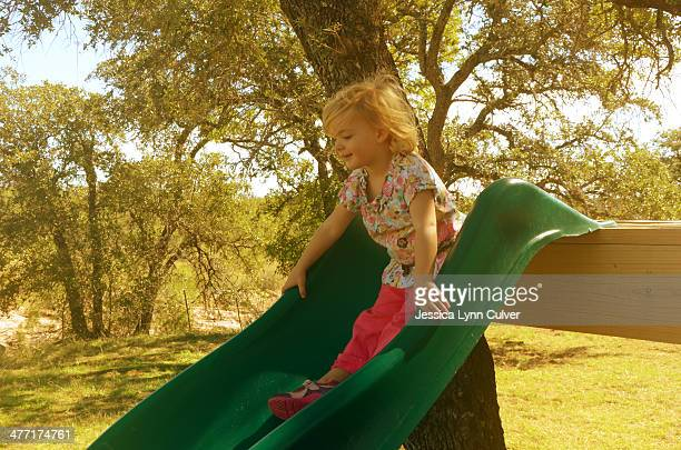 Young girl on a green slide