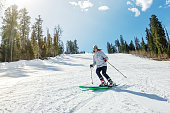 Young girl on alpine skiing on a snowy track against the sky.
