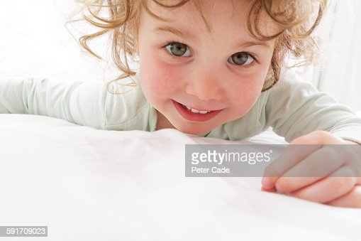 Young girl on bed looking into camera