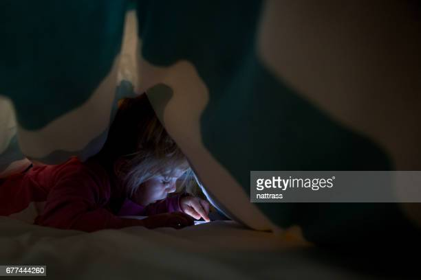 Young girl on cell phone under duvet