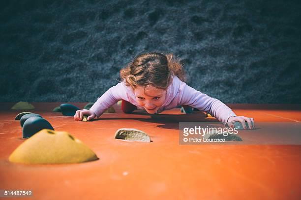 Young girl on climbing wall