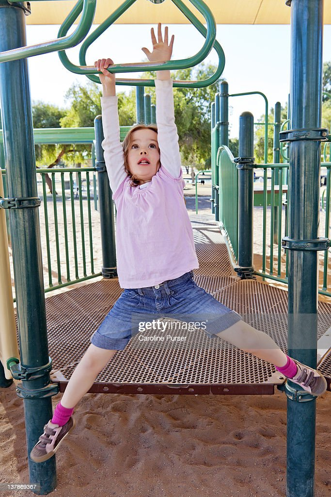 Young girl on monkey bars, look of anticipation : Stock Photo