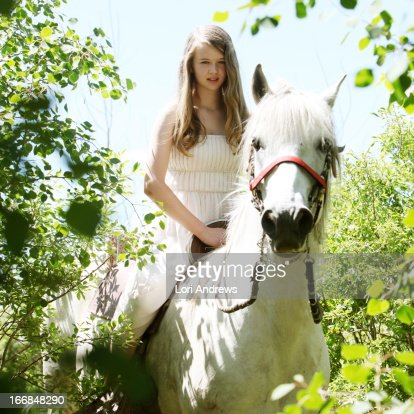 Young girl on white horse in the woods
