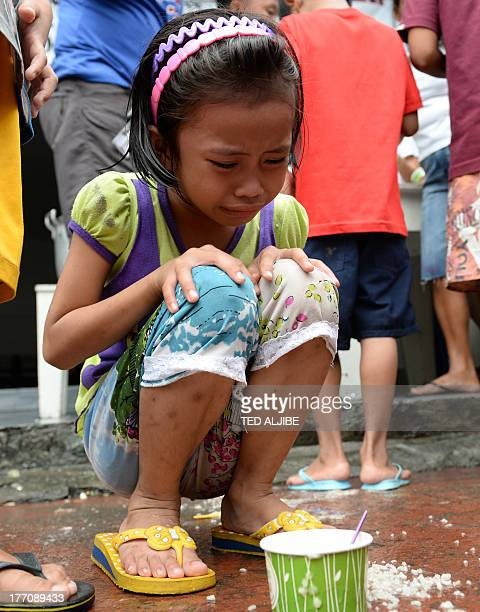 A young girl one of the thousands affected by flooding due to heavy rains exacerbated by Tropical Storm Trami cries after a cup of congee slipped...