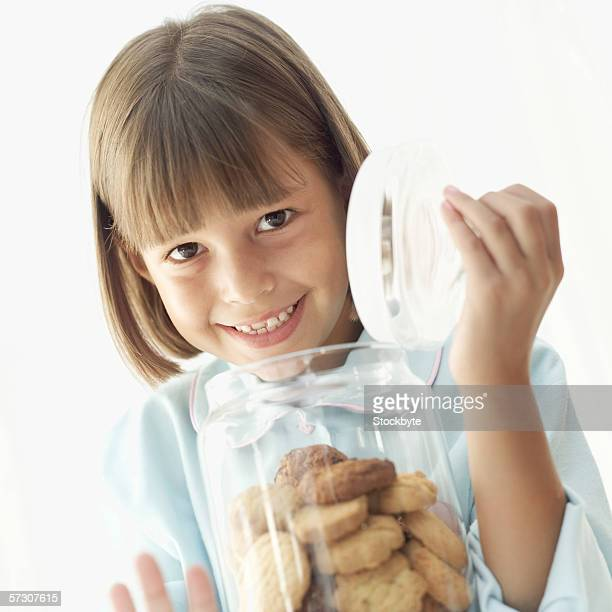 Young girl (8-9) opening a jar of cookies