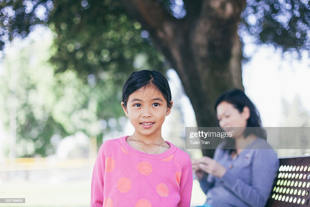 young girl outdoor with mother in the background : Stock Photo