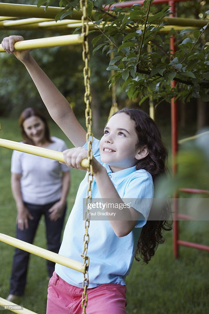 Young girl outdoors at playground climbing with senior woman in background : Stock Photo