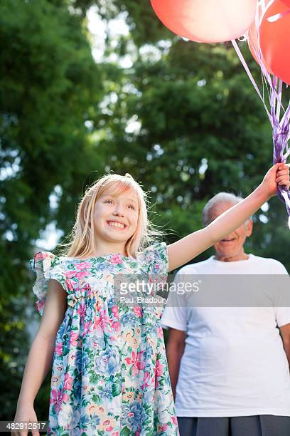Young girl outdoors holding balloons and smiling with senior man in background