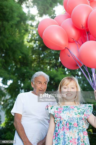 Young girl outdoors holding balloons and smiling with senior man